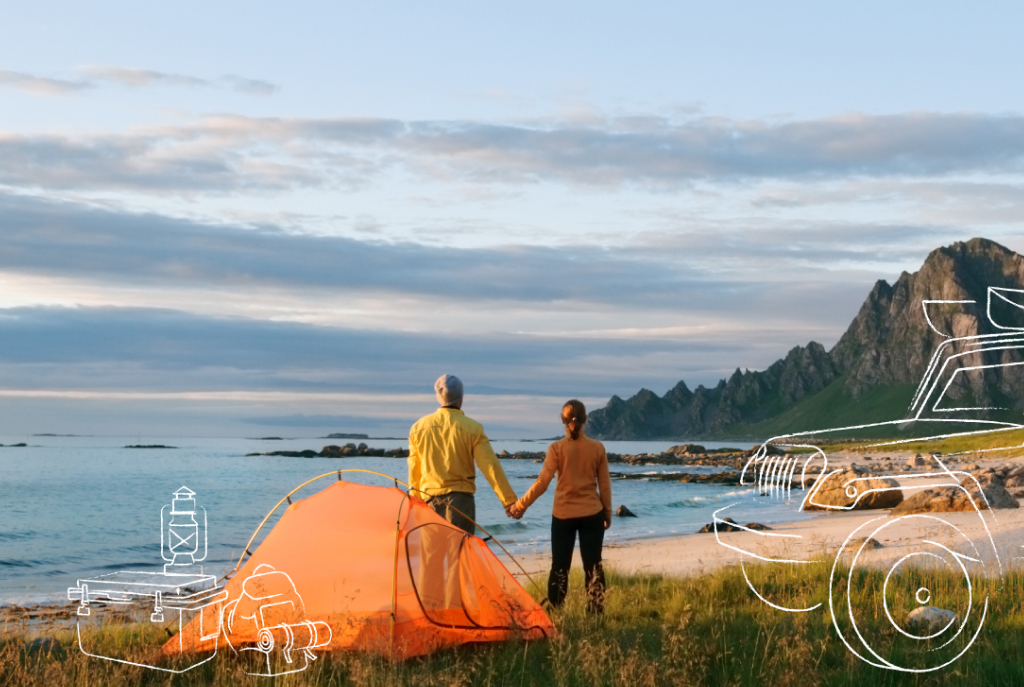 couple holding hands by tent on the beach