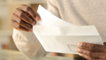 man opening an envelope and pulling out a letter