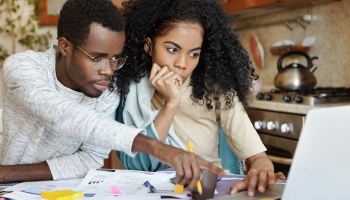 Couple reviewing monthly statements and planning a financial budget