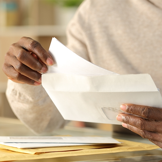 person opening an envelope with stimulus check