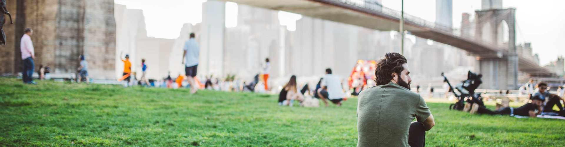 man sitting in a park beneath the Brooklyn Bridge